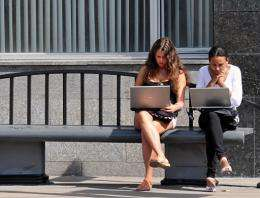 Russian teenage girls work on laptop computers while wating for a public bus in Moscow