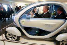 Spanish Minister of industry Miguel Sebastian (C) sits in an electric car with Jean Pierre Laurent