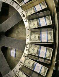 Stacks of one dollar bills pass through a machine at the Bureau of Engraving and Printing in Washington, DC