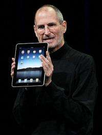 Steve Jobs holds up the new iPad