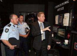 Symantec VP Craig Scroggie (R) launches a display with police commissioners Neil Gaughan (L) and Michael Phelan