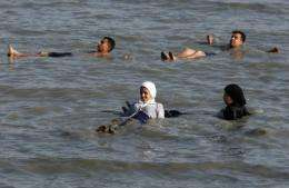 Two Palestinian Muslim women swim in their clothes in the waters of the Dead Sea