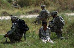 US soldiers guard a detained Iraqi suspected of ties to Al-Qaeda on the southern outskirts of Baghdad, in 2007