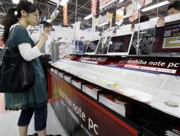 A customer checks Japanese electronics giant Toshiba notebook computers at an electronics shop