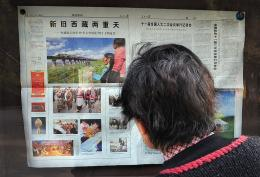 A woman reads a state media newspaper