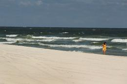 A woman walks the beach in Gulf Shores, Alabama, in 2010