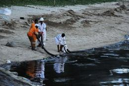 Emergency workers attempt to clear the crude oil slick