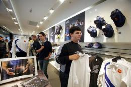People look at French and English rugby union national team jerseys at the Champs Elysee Nike store