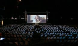 People watch a film in an open-air cinema