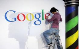 A stand builder fixes a logo at the Google stand