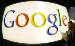 A visitor walks past the logo of internet search engine giant Google at a trade fair