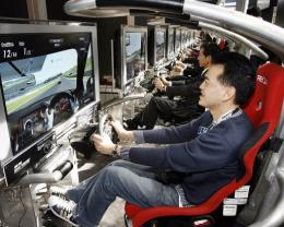 Visitors play Sony Computer Entertainment's latest driving video game