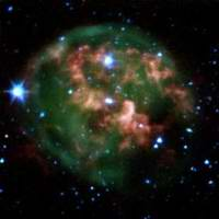 This false-color image from NASA's Spitzer Space Telescope shows a dying star (center) surrounded by a cloud of glowing gas and
