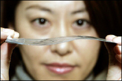 A NEC employee shows off an ultra-thin, flexible battery