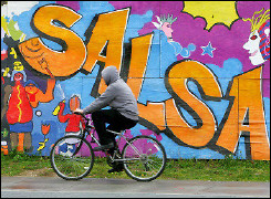 A man rides his bicycle past a colourful mural in the Columbia Heights area of Washington