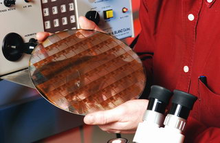 Professor John Cressler is reflected in a 200 GHz silicon-germanium integrated circuit wafer.
