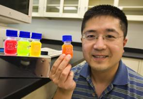 Frank Chen holds a bottle of quantum dots.