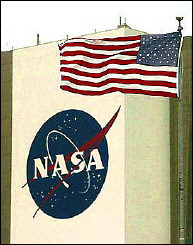 A flag stands out at Kennedy Space Center next to the NASA logo