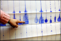 An official at a seismology center points to earthquake readings