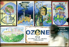 A man (R) walks past a display of paintings by students for the preservation of the ozone layer