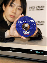 A Toshiba employee displays the prototype model of the HD DVD player and its 30GB disc