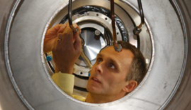 Philip Harris inspects the liquid helium supply pipes on the neutron Electric Dipole Moment cryostat