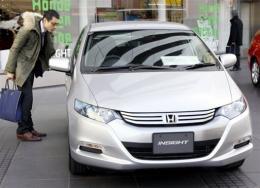 A customer admires a Honda Motor's hybrid vehicle