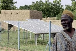 A man pictured next to solar panels in a village in Niger in 2004
