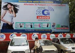 A man talks his mobile phone in front a government telecommunication billboard