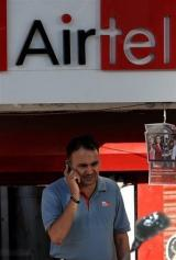 An Indian man talks on his mobile phone next to a Bharti Airtel sign in New Delhi