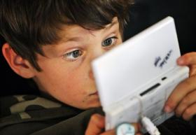 A participant of a game tournament is seen behind his Nintendo DS