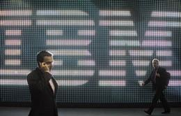 A visitor speaks on his cellphone as he walks past a giant screen near an IBM display