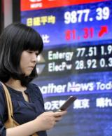 A woman uses her mobile phone near a share prices board in Tokyo