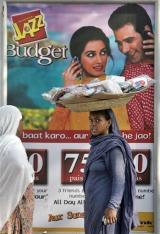 A woman walks in front of a mobile phone company advertisement in Islamabad