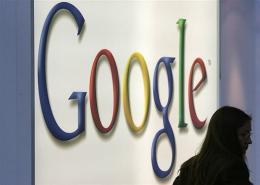 A woman walks past a Google logo