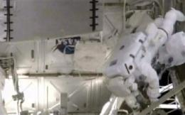 Baby can wait as expectant dad finishes spacewalk (AP)