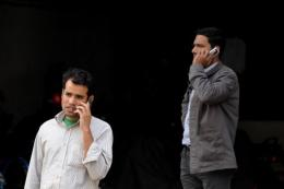 Bangladeshi pedestrians speak on their cellular telephones as they walk through a commercial district in Dhaka