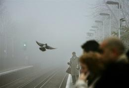 Commuters wait on the platform shrouded by fog in London