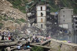 Former residents and tourists look at the damage in the quake-stricken town of Beichuan, China