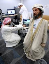 Ibn Sina sports a white cloak, golden-trimmed robe, a turban and grey beard