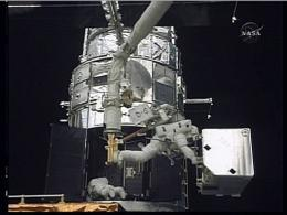 In this image obtained from NASA video, astronauts work to service the Hubble space telescope