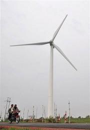 Men share a motorcycle riding past a wind power plant in Zhangbei