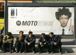 Men sit on the sidewalk in front of a Motorola advertising billboard in Beiijng