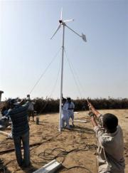 Pakistani technicians install a wind turbine on the island of Kharochhan