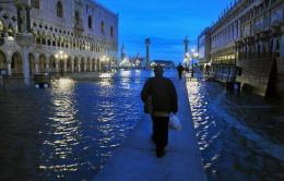 People walk on a plateform on the flooded Piazza San Marco (St Mark's square) in Venice