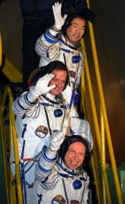 Top-bottom: Soichi Noguchi, Timothy J. Creamer and Oleg Kotov wave before boarding a Soyuz TMA-17 spacecraft