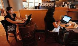 Women use their laptop computers at a wireless cafe in Beijing