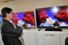 A journalist compares the competing 3-D televisions of Samsung(L) and LG(R)