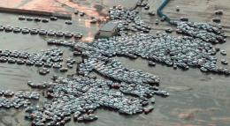 An aerial shot shows vehicles ready for shipping being carried by a tsunami tidal wave