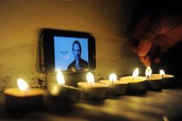 Candles are lit in tribute to Steve Jobs outside an Apple store